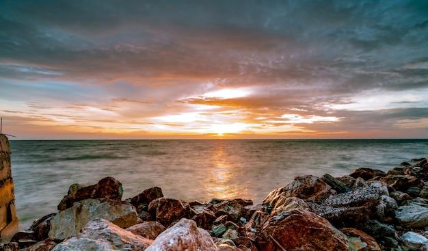 Rocce sulla spiaggia di pietra al tramonto. cielo al tramonto bellissima spiaggia. crepuscolo mare e cielo. mare tropicale al crepuscolo. cielo e nuvole drammatici. calma e rilassa la vita. paesaggio naturale.