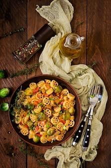Rocchetti di verdure vegetariano pasta con cavoletti di bruxelles, pomodoro, melanzane e paprika in ciotola marrone sul tavolo di legno. vista dall'alto