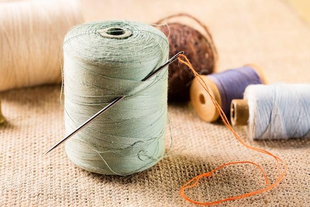 Rocchetto di filo con ago con altri rocchetti su tela