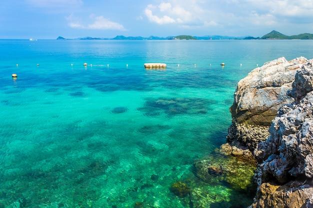 Roccia di isola tropicale sulla spiaggia con cielo blu.