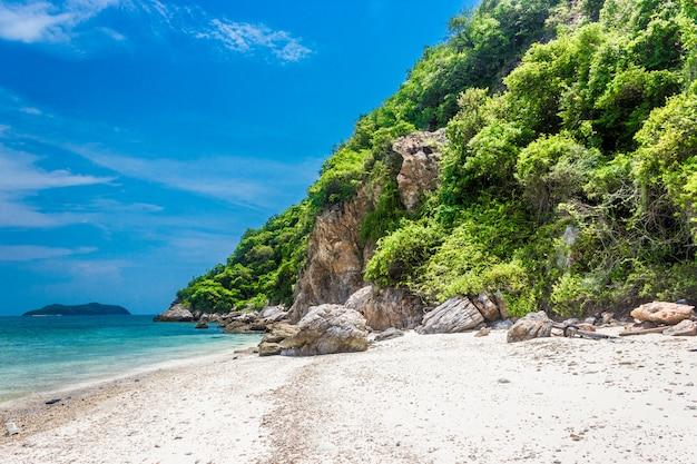 Roccia di isola tropicale sulla spiaggia con cielo blu
