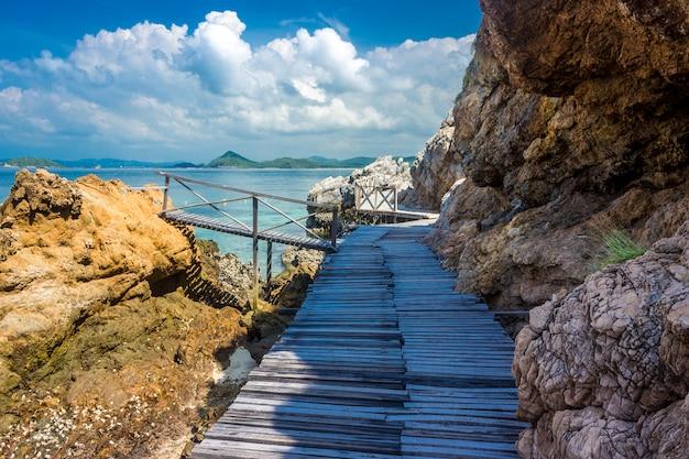 Roccia tropicale dell'isola e ponte di legno sulla spiaggia con cielo blu.