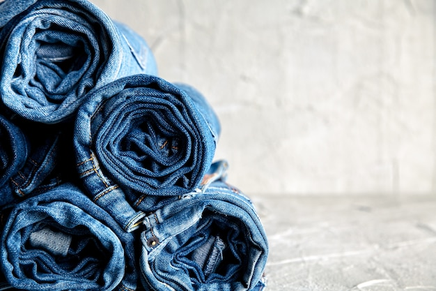 Roll blue jeans denim su sfondo grigio
