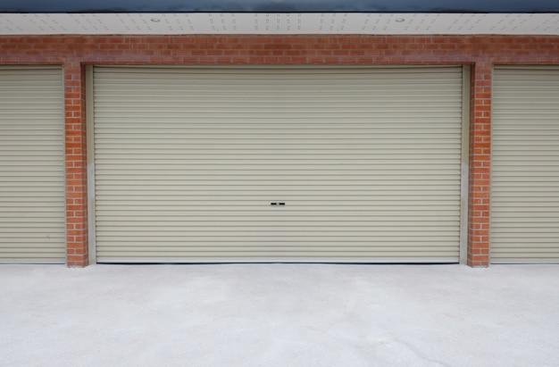 Roll porta in acciaio o porta dell'otturatore e pavimento in cemento al di fuori dell'edificio di parcheggio di casa.