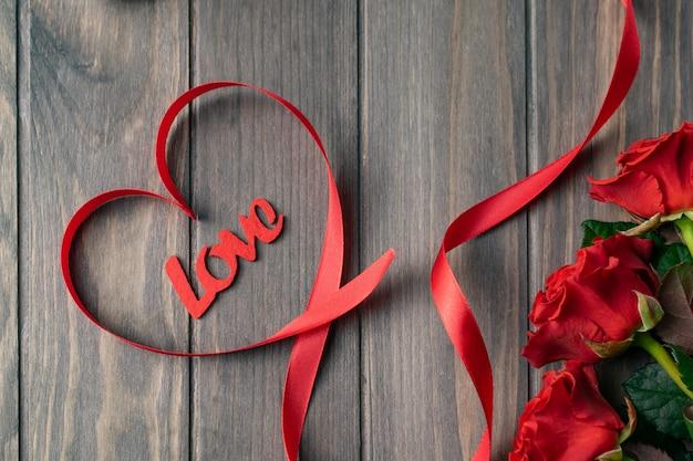Romantica carta di sfondo in legno san valentino con bouquet di belle rose rosse e lettere d'amore