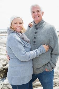 Romantica coppia senior sulla spiaggia rocciosa