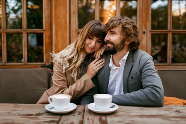 Romantica donna pensosa con lunghi capelli ondulati che abbraccia il marito con la barba. coppie eleganti che si siedono nella caffetteria con cappuccino caldo.