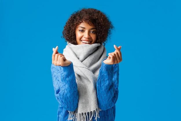 Romantica e sciocca fidanzata afro-americana, taglio di capelli afro, maglione e sciarpa invernali, in attesa di san valentino presente e data, mostrando segni di cuore coreano e sorridente, blu