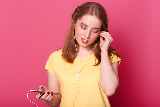 Romantica giovane donna con una pettinatura carina e trucco professionale che fissa il suo auricolare a destra, tenendo in mano un leggero cellulare. modello pone isolato su rosa brillante.
