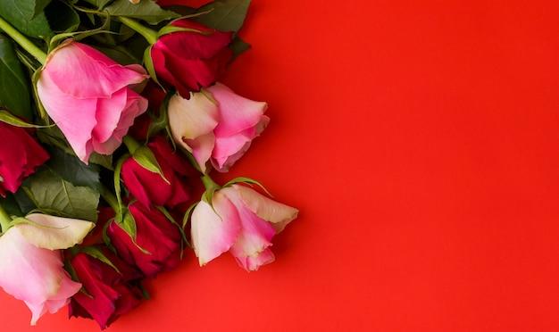 Romantica natura morta, rose rosse su sfondo rosso. concetto di cartolina per la festa della donna e san valentino. copia spazio.