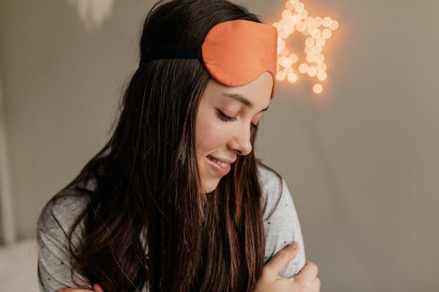 Romantica ragazza timida con i capelli scuri che indossa la maschera per dormire sulla testa che riposa a casa. mattina sveglia a casa