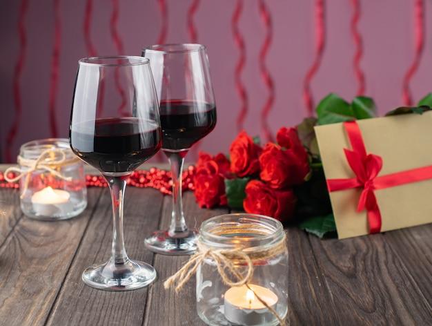 Romantica serata accogliente con vino, fiori, candele e regalo