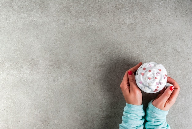 Romantico, san valentino. ragazza che beve cioccolata calda con panna montata e cuori dolci, mani nell'immagine, vista dall'alto,