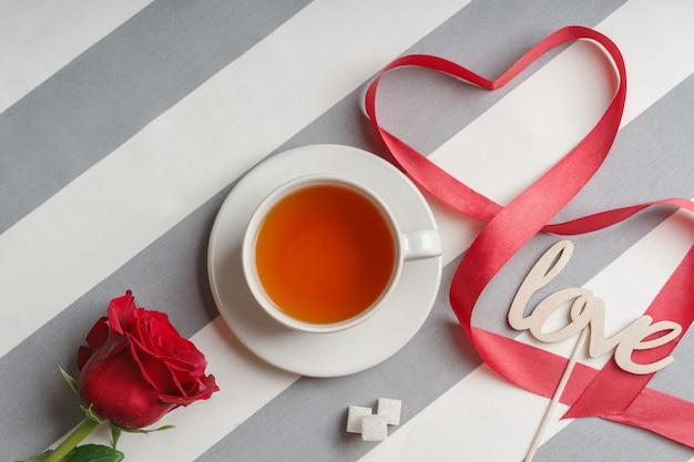Romantico still life con una tazza di tè e attributi di vacanza rosso brillante.