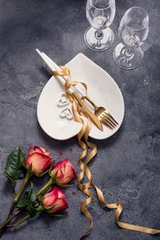 Romantico tavolo da pranzo con rose, bicchieri di champagne, piatto a forma di cuore e nastro dorato, san valentino o cena romantica