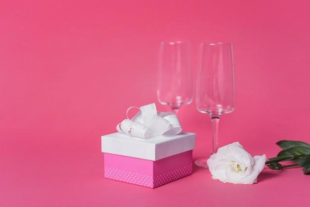 Rosa bianca; confezione regalo e bicchieri flute di champagne su sfondo rosa