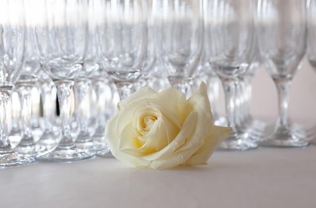 Rosa bianca sul tavolo con bicchieri di champagne, evento di nozze