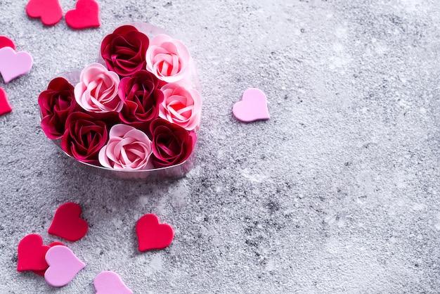 Rosa brillante e rose rosse fatte di scaglie di sapone con cuori su pietra, in una scatola a forma di cuore.
