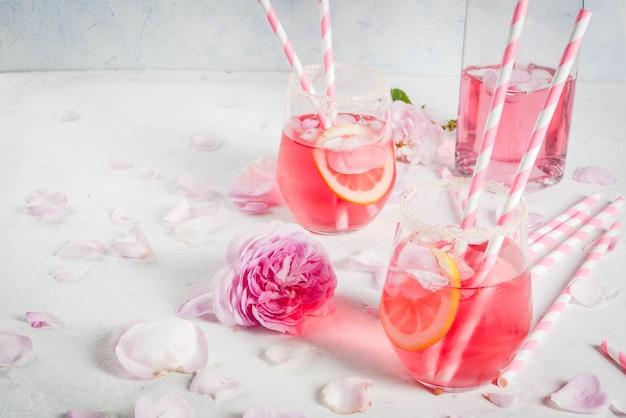 Rosa chiaro rosa cocktail, con vino rosato, petali di rosa tea e limone su un tavolo di cemento bianco pietra.