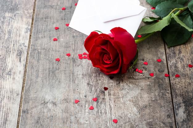 Rosa con busta e cuori sullo spazio di copia in legno sullo sfondo