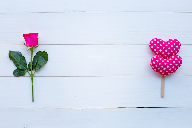 Rosa e cuori di san valentino su fondo di legno bianco.