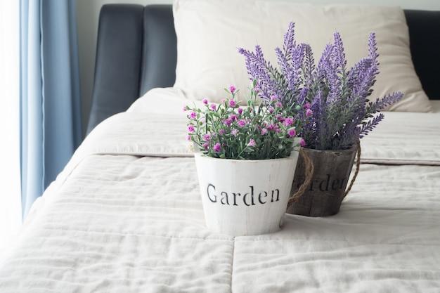 Rosa e fiori di lavanda sul letto nella camera da letto.