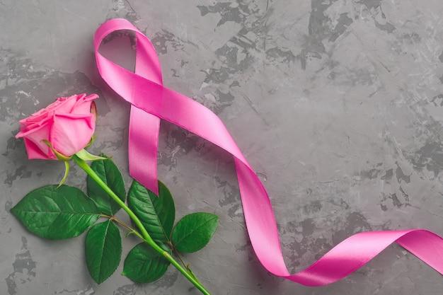 Rosa e nastro di rosa su fondo concreto. concetto