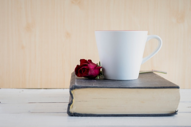 Rosa, libro e tazza di caffè sul tavolo di legno bianco