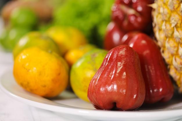 Rosa mela e arancia sul piatto bianco.