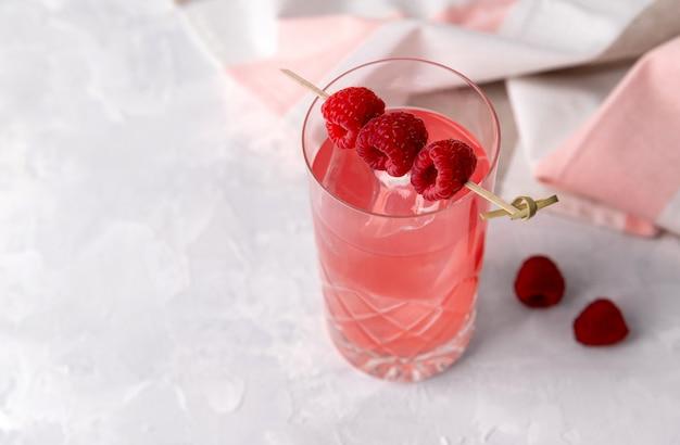Rosa rosa cocktail ghiacciato con lampone in cristallo sul tavolo