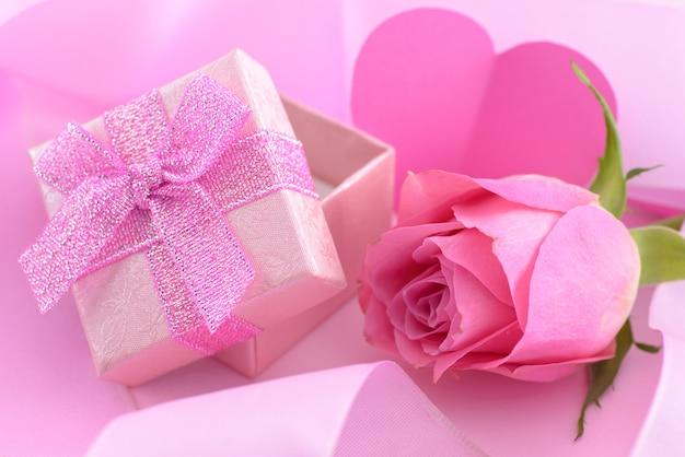 Rosa rosa e una confezione regalo con cuori, sullo sfondo del giorno di san valentino