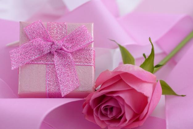 Rosa rosa e una confezione regalo, sullo sfondo del giorno di san valentino