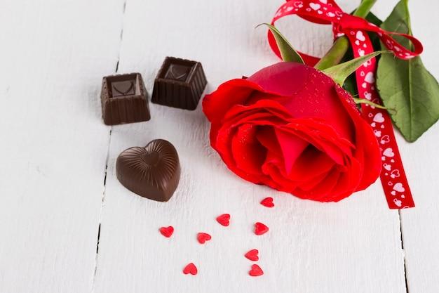 Rosa rossa, cioccolato su un fondo di legno bianco