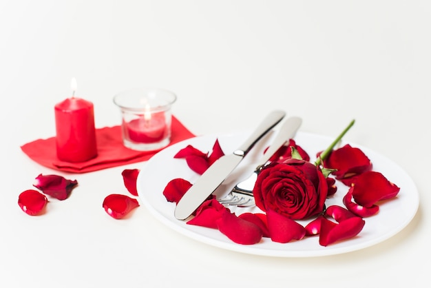 Rosa rossa con posate sul piatto
