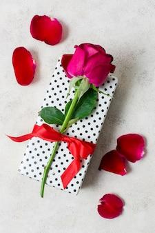 Rosa rossa del primo piano sopra il regalo