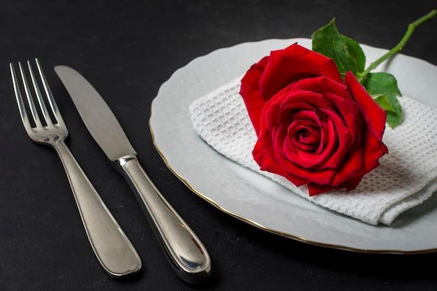 Rosa rossa del primo piano su un piatto con la coltelleria