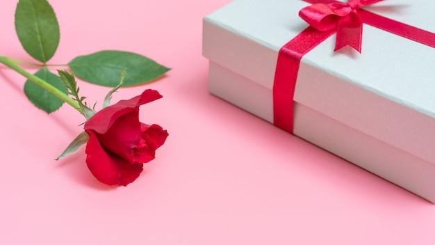 Rosa rossa e confezione regalo su uno sfondo rosa.