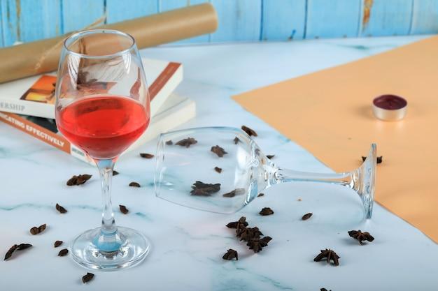 Rosa rossa in un bicchiere e un bicchiere di vino vuoto sul cartone
