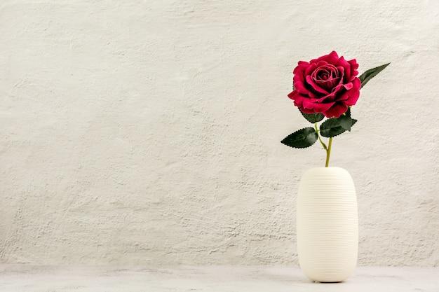 Rosa rossa in vaso di ceramica bianca sul tavolo.