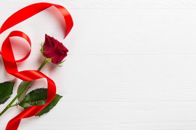 Rosa rossa, nastro sul tavolo bianco.