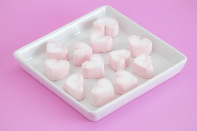 Rosa sentire marshmallow, dolci cuori di marshmallow su sfondo rosa. regalo di san valentino