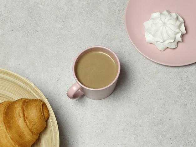 Rosa tazza di cappuccino con marshmallow e croissant su sfondo di granito