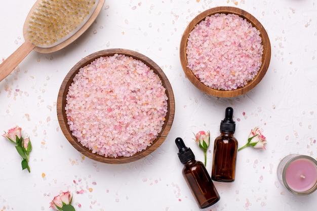 Rose bagno di sale e bottiglie di olio naturale su bianco