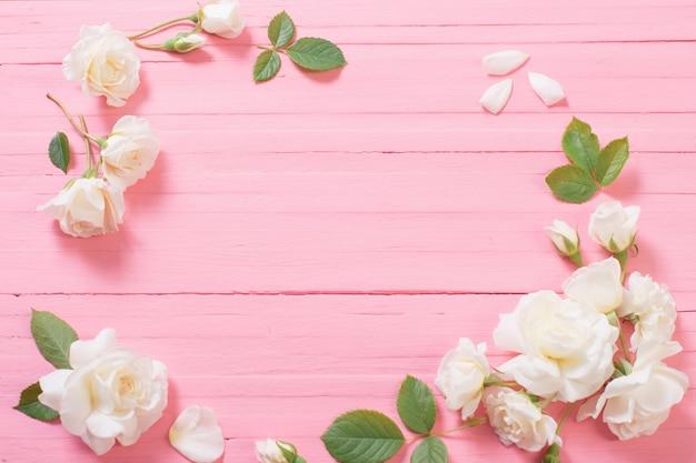Rose bianche su fondo di legno rosa