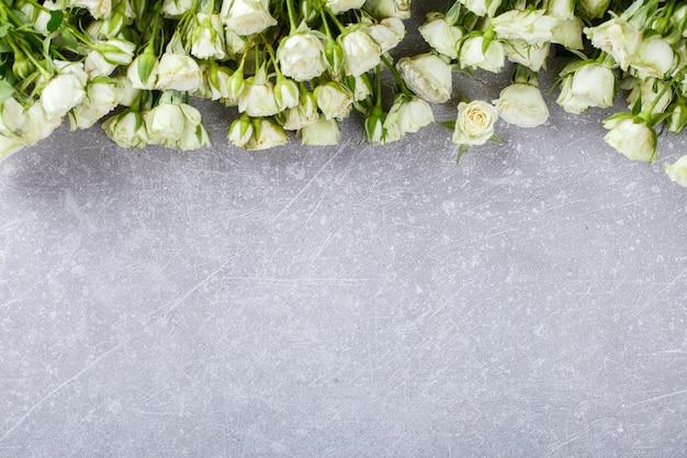 Rose bianche su una priorità bassa grigia. freschezza, piccoli fiori