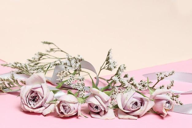 Rose d'epoca e fiori bianchi su sfondo rosa