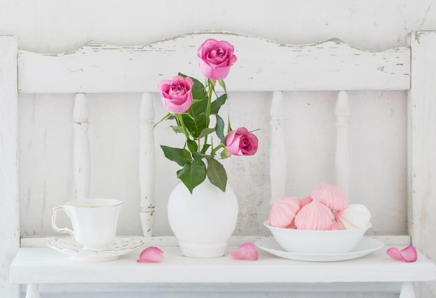 Rose del perno in vaso e stoviglie sullo scaffale di legno bianco