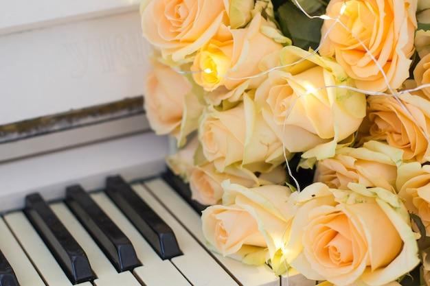 Rose di pesca con ghirlande su un pianoforte bianco