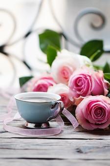Rose e coffe rosa sulla tavola di legno