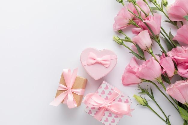 Rose e contenitori di regalo rosa su fondo bianco